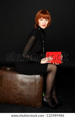 Full length portrait of woman with book sitting on suitcase