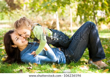 Full length portrait of woman with child lying on fall leaves in autumn park - stock photo