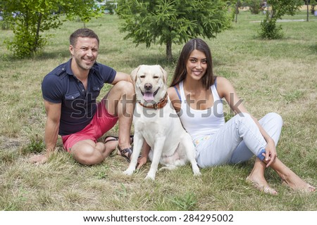 Full length portrait of Young adult happy Couple sitting with white Dog Labrador at summer park on fresh green grass background against spring trees in perspective Empty copy space for inscription