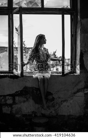 Full length portrait of Young adult woman sit on windowsill near dirty glass open window. Girl's hand lie on dirt frame. Female wear blue dress with flowers pattern - stock photo