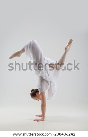 Full length portrait of young and beautiful modern style dancer doing split handstand isolated on white background, studio shot - stock photo