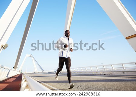 Full length portrait of young athlete jogging in the city at beautiful sunrise - stock photo