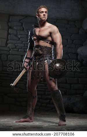 Full length portrait of young attractive warrior gladiator with muscular body holding shield and axe, posing on dark background. Concept of masculine power, strength - stock photo