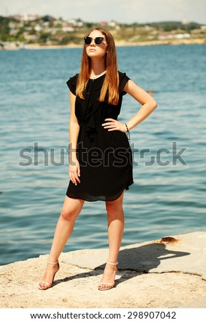 Full length portrait of young beautiful pretty girl posing outdoors