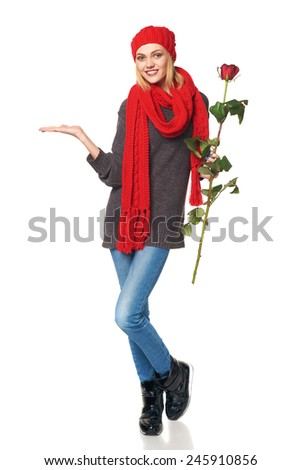 Full length portrait of young beautiful woman holding red rose and showing open hand palm with copy space for product or text, over white background
