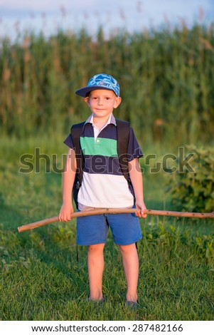 Full Length Portrait of Young Boy Wearing Backpack Standing Outdoors in Field and Holding Large Walking Stick - stock photo