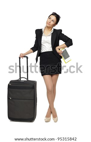 Full length portrait of young business woman standing with her travel bag, holding the tickets with passport, looking sideways at blank copy space, isolated on white background