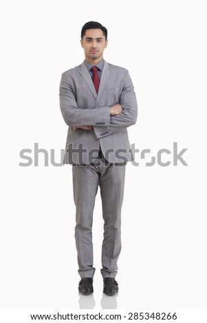 Full length portrait of young businessman with arms crossed standing against white background