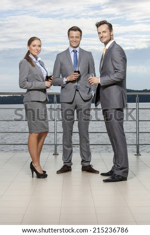 Full length portrait of young businesspeople holding wineglasses on terrace - stock photo