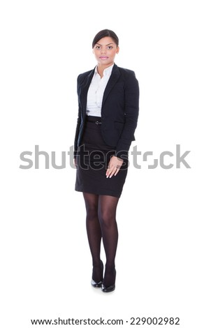 Full length portrait of young businesswoman standing over white background - stock photo