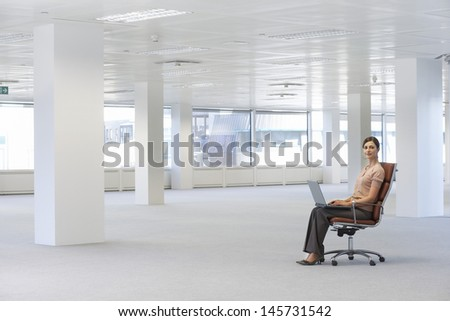 Full length portrait of young businesswoman using laptop on chair in empty office space - stock photo