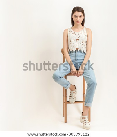 Full length portrait of young calm beautiful brunette woman posing for model tests against white background sitting on bar stool - stock photo