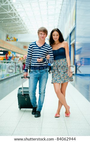 Full-length portrait of young couple in love walking with suitcase around international airport.
