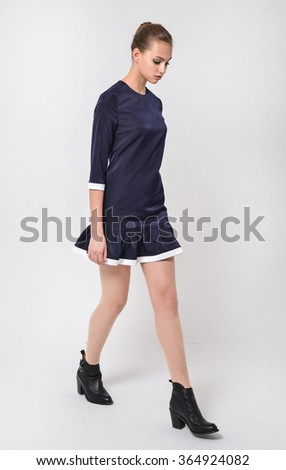 full-length portrait of young fashion model walking in studio   - stock photo