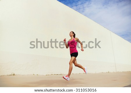 Full length portrait of young fit woman in tracksuit with a perfect figure jogging fast against cement wall with copy space area for your text message or content, female runner working out outdoors - stock photo