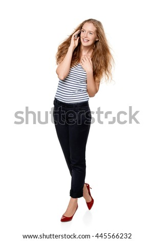 Full length portrait of young, happy beautiful woman talking on cell phone, over white background - stock photo