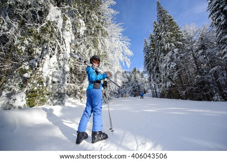 Full length portrait of young happy female skier on a ski slope in the winter forest on a sunny day. Woman is holding skis on her shoulder smiling and looking towards the camera. Ski resort. Bukovel - stock photo
