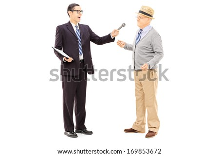 Full length portrait of young man conducting survey on middle aged man with microphone in his hand, isolated on white background  - stock photo
