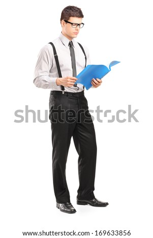 Full length portrait of young man reading papers, isolated on white background - stock photo