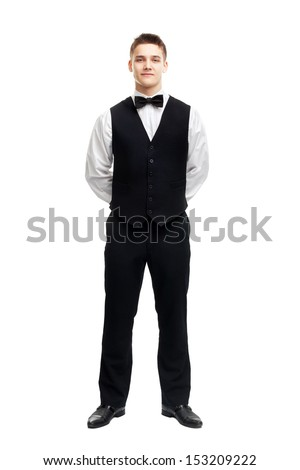 Full length portrait of young smiling waiter standing with hands behind his back isolated on white background - stock photo