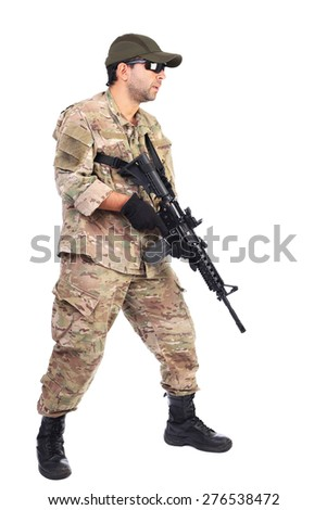 Full length portrait of young soldier in army clothes holding a weapon against white background - stock photo