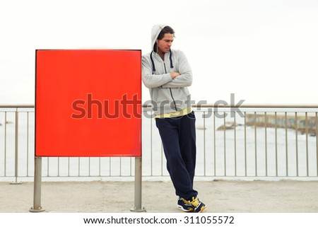 Full length portrait of young sportsman resting after workout outdoors while standing near the board ads with copy space area for your text message or information,male jogger rest after run outside - stock photo