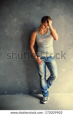 Full length portrait of young stylish man wearing undershirt and jeans leaning to gray textured wall - stock photo