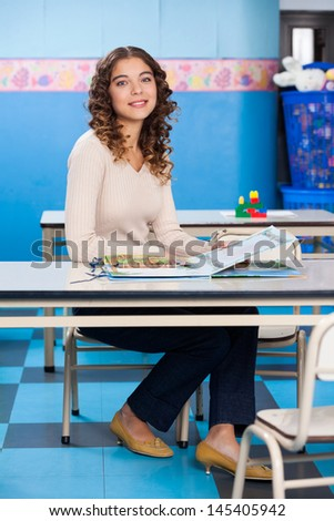 Full length portrait of young teacher with popup book sitting at desk in preschool - stock photo