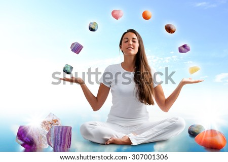 Full length portrait of young woman dressed in white doing yoga with precious gemstones.Conceptual image with colorful gemstones floating around girl. - stock photo