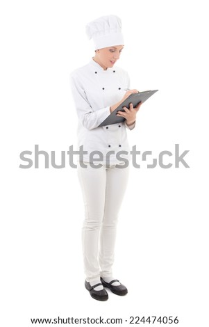 full length portrait of young woman in chef uniform writing something in clipboard isolated on white background - stock photo