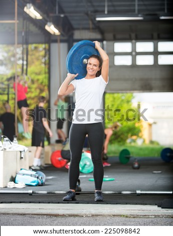 Full length portrait of young woman lifting barbell plate in box - stock photo
