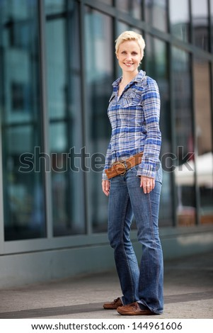 Full length portrait of young woman smiling by building - stock photo