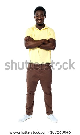 Full length portrait smiling african guy standing with arms crossed - stock photo