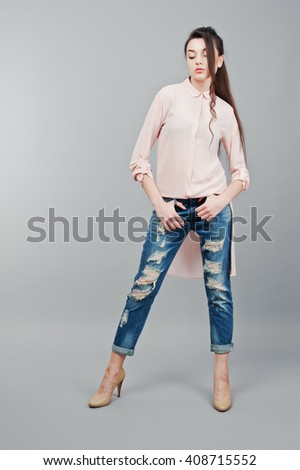 Full-length portrait young brunette girl wearing in pink blouse, ripped jeans and cream shoes .Fashion studio shot - stock photo