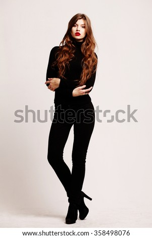 Full-length portrait young elegant woman in a black turtleneck and black skinny jeans. Fashion studio shot. Fashion model - stock photo