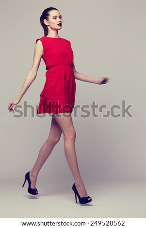 Full-length portrait young elegant woman in red dress, fashion studio shot  - stock photo