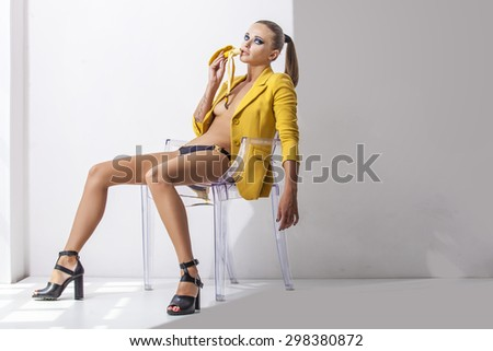 Full-length portrait young elegant woman in the yellow jacket, shorts and shoes with heels on a transparent chair with banana. Fashion studio shot. - stock photo