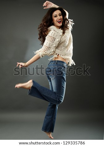 Full length pose of happy young woman, jumping of joy, on gray background