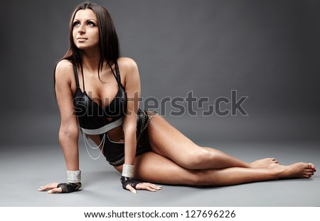 Full length profile of hot Latin dancer in latex lingerie sitting on the ground, looking up - stock photo