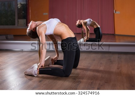 Full Length Profile of Young Woman Wearing Exercise Clothing Stretching Backwards in Ustrasana Camel Yoga Pose in Dance Studio with Mirrored Wall and Reflection in Background - stock photo