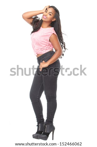Full length profile portrait of a beautiful young woman smiling with hand in hair - stock photo