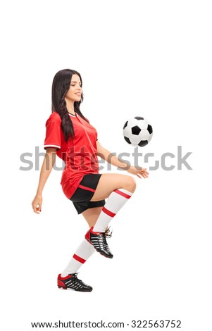 Full length profile shot of a female soccer player juggling a ball on her knee isolated on white background - stock photo