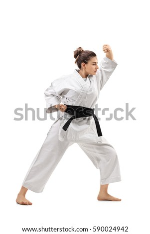 Full length profile shot of a girl wearing a kimono practicing karate isolated on white background