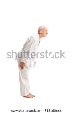 Full length profile shot of a senior man in a white kimono bow down isolated on white background - stock photo