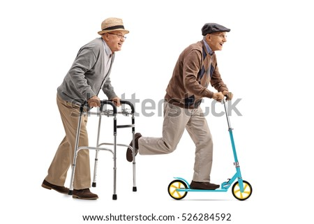 Full length profile shot of a senior walking with a walker and another senior riding a scooter isolated on white background