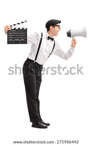 Full length profile shot of a young movie director holding a clapperboard and shouting on a megaphone isolated on white background - stock photo