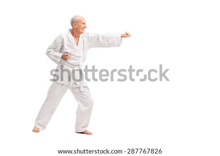 Full length profile shot of an old man in a white kimono practicing karate isolated on white background  - stock photo
