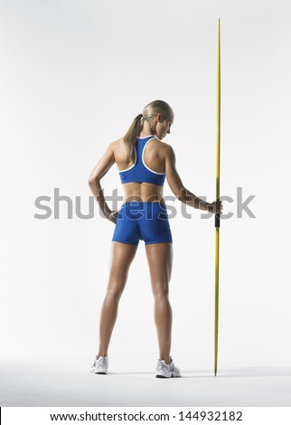 Full length rear view of a female athlete holding javelin against white background - stock photo