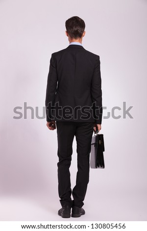 full length rear view of a young business man standing with a briefcase in his hand, on gray - stock photo