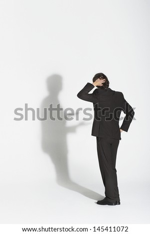 Full length rear view of a young businessman arguing with own shadow against white background - stock photo